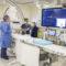 Au laboratoire de cathétérisme cardiaque de l'HGJ, les infirmières Tracy Hodge (à gauche) et Zaralyne Lahorra discutent de procédures cliniques avec le Dr Nathan Messas. Pendant le traitement, le patient est allongé sur la table et l'appareil biplan (au fond, à gauche) est ramené vers l'avant. Les deux scanneurs – le premier au niveau du thorax et le second au niveau de la tête entre Mme Hodge et le Dr Messas -- prennent des images en temps réel de deux angles différents et les projettent sur l'écran à droite.