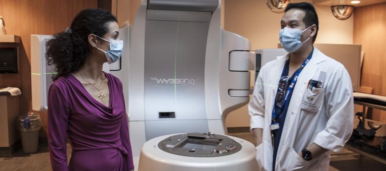 La Dre Magali Lecavalier-Barsoum consulte le technologue Dennis Ip au sujet de l'accélérateur linéaire de la Division de radio-oncologie qui fournit la radiothérapie aux patients atteints de cancer.