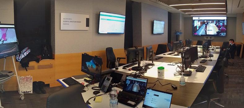 Vue grand-angle du centre de commandement au cours de la première étape, dans la salle de conférence de l'HGJ, et des nombreux écrans contenant des données en temps réel sur le flux des usagers des soins de santé dans les installations du CIUSSS du Centre-Ouest-de-l'Île-de-Montréal.