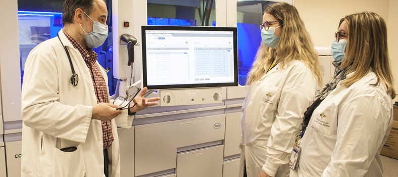 Le Dr Jerry Zaharatos parle de l'instrument cobas 8800, mis en service récemment à l'HGJ, et de sa fonction d'analyse automatisée des écouvillons des tests de dépistage de la COVID-19 avec (au centre) Melissa Tomkinson, chef du Laboratoire de microbiologie et génétique et Argyroula Terzidis, coordinatrice administrative, Division de microbiologie et biologie moléculaire. (Cliquez sur l'une des photos pour l'agrandir.)