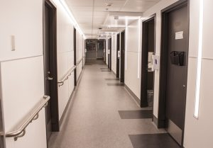 The main corridor of the new Wellness in Aging Centre is brightly illuminated not just by ceiling fixtures, but vertical lighting strips on the walls.