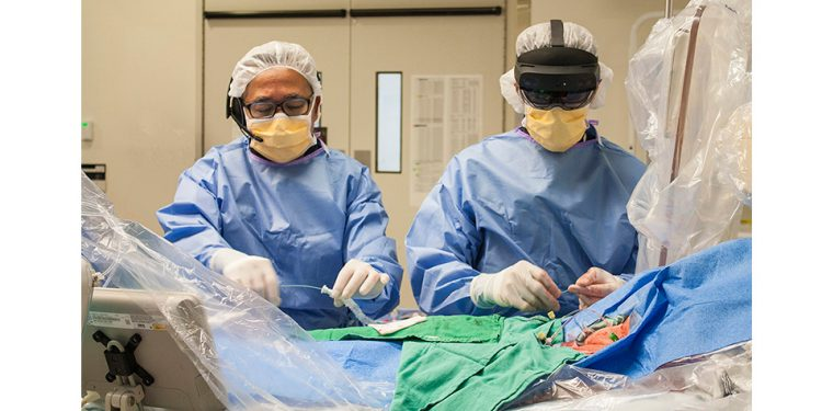 Le Dr Ali Abualsaud (à droite), un cardiologue interventionnel, effectue une intervention à effraction minimale à l'HGJ pour remplacer la valve aortique défaillante d'une patiente. Le Dr Felix Ma, un chirurgien cardiaque travaille avec le Dr Abualsaud. Le Dr Abualsaud porte un casque HoloLens, qui le relie à Caroline Merineau, une spécialiste clinique de Medtronic Canada, à Trois-Rivières, grâce à une plateforme de communication développée par Auger Groupe-Conseil. La technologie numérique du casque est tellement avancée que le Dr Abualsaud et Madame Merineau ont presque l'impression d'être côte à côte dans la salle d'opération hybride à l'HGJ, pendant qu'ils parlent des particularités de la valve artificielle, fabriquée par Medtronic. (Cliquez sur l'une des photos pour l'agrandir.)