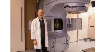 Dr. Khalil Sultanem, Acting Chief of Radiation Oncology, with one of his Division's linear accelerators. (Click on this or any photo to enlarge it.)