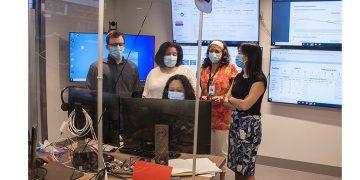 Au Centre de commandement numérique de l'HGJ, Suzette Chung (assise), responsable de la Planification des congés de l'Hôpital, et (à partir de la gauche) Matthew Wener, physiothérapeute et membre de l'équipe du Guichet d'accès aux lits de réadaptation en santé physique et soins respiratoires, Arleyne Coombs, chef des Services sociaux, Marcia Da Silva, travailleuse sociale à la direction de Santé mentale et dépendance, et Thu Hanh Ngo Nguyen, chef d'administration du programme Accès, discutent du congé ou du transfert des patients. Les écrans en arrière-plan affichent les données à jour sur l'état et les progrès des usagers des services de santé de l'HGJ et des autres installations du CIUSSS. (Cliquez sur la photo pour l'agrandir.)